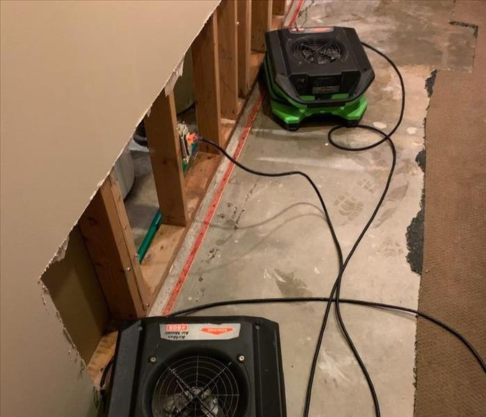 a room with flood cut drywall with green servpro humidifiers and air movers