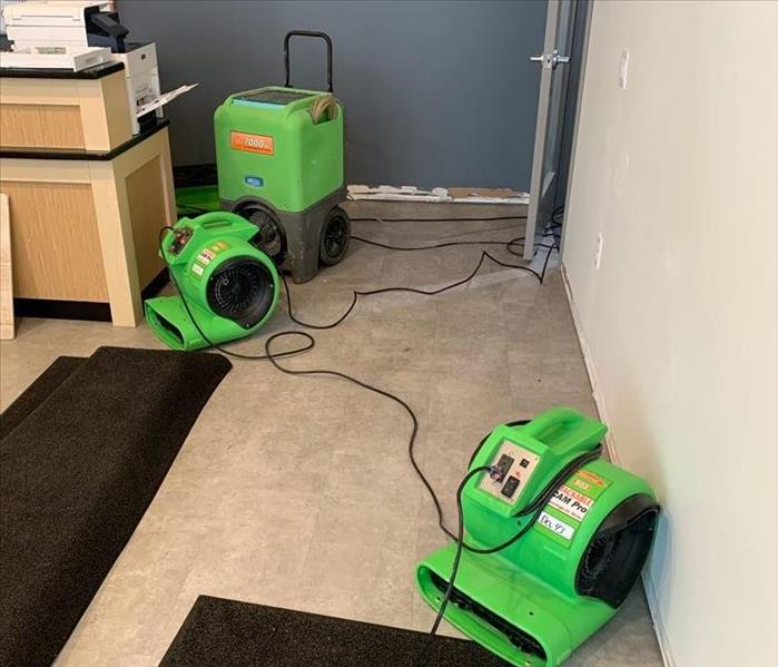 a commercial business in fitchburg, wi with green servpro drying equipment