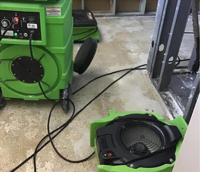 concrete floors with green air movers and humidifier adjacent to a removed water heater that malfunctioned