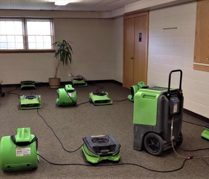 commercial carpet being dried with many green air movers and a large green humidifier