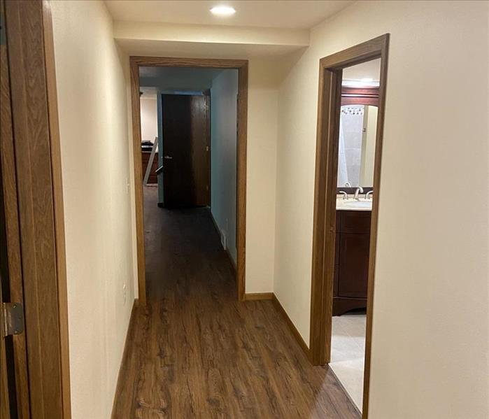 newly remodeled basement hallway with wood floors and freshly painted drywall and trim