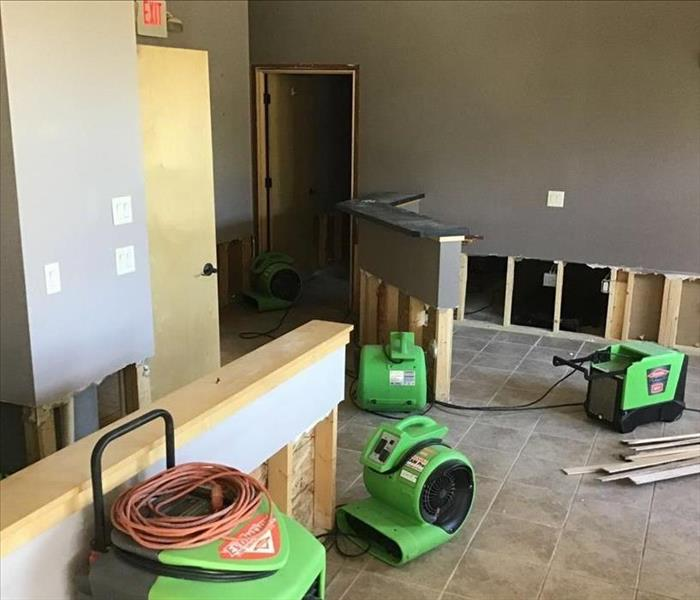 a salon with flood cut walls from water damage from putting a fire out. Servpro equipment is in place to dry the property
