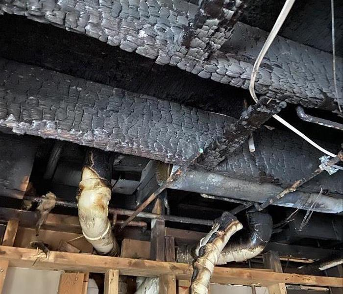 a charred fire damaged ceiling caused from an electrical fire