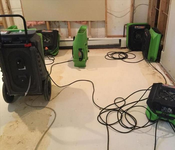 a basement with servpro air movers and dehumidifiers to dry out a water damaged basement