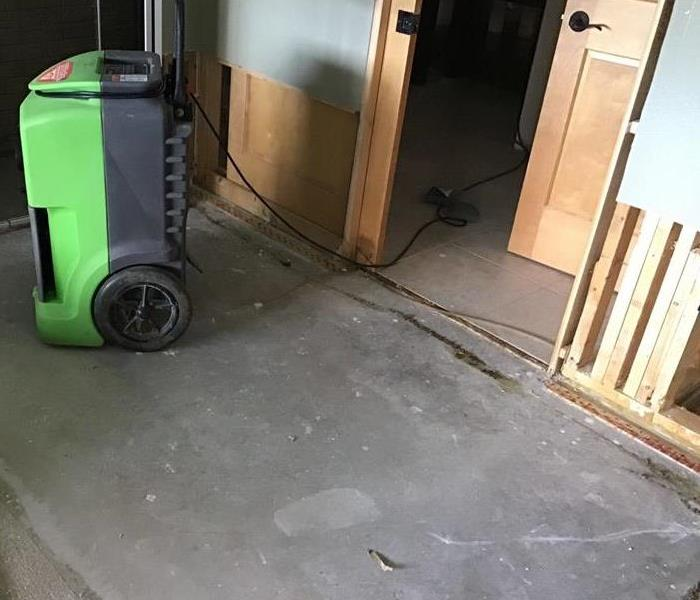a bedroom with flood cut walls after storm damage there is also a green SERVPRO dehumidifier
