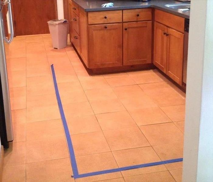 a kitchen with wood cabinets and flooring with a blue tape line is outlining the damaged flooring