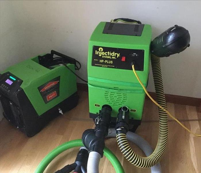 two servpro green injector dry machines used to dry and save buckled hardwood floors
