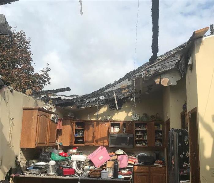 a kitchen that has been severely damaged from a fire, the roof is exposed as the fire engulfed it, fire damage kitchen items