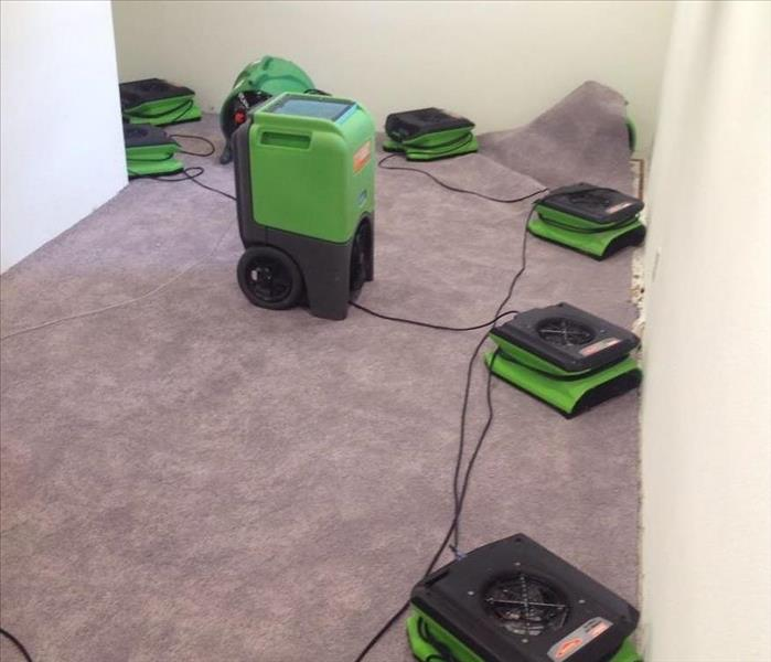 servpro drying fans and dehumidifiers drying out a basement from storm damage