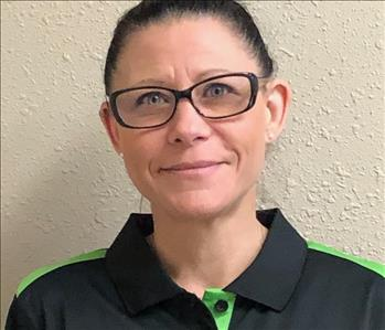 head shot of a woman with dark hair, glasses in a SERVPRO hero uniform