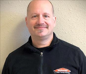 a headshot of a Caucasian man in a black zip up pullover with a SERVPRO logo on it