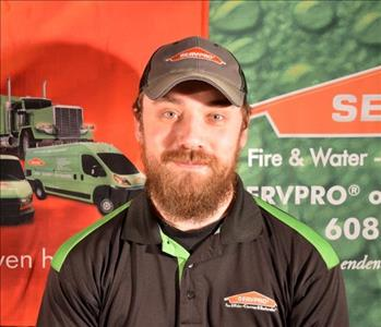 A brown haired male with beard wearing a SERVPRO uniform