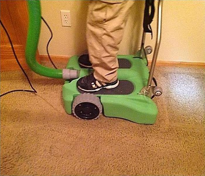 a man in khaki pants and a black polo using a servpro rover to extract water from flooded carpet