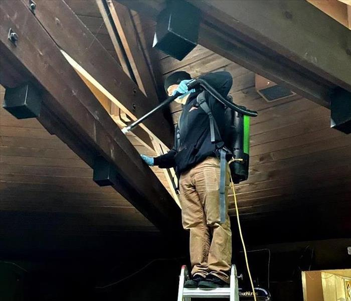 a man with khaki pants and black SERVPRO top standing on a ladder with a Hepa Vacuum cleaning soot particles from a fire job