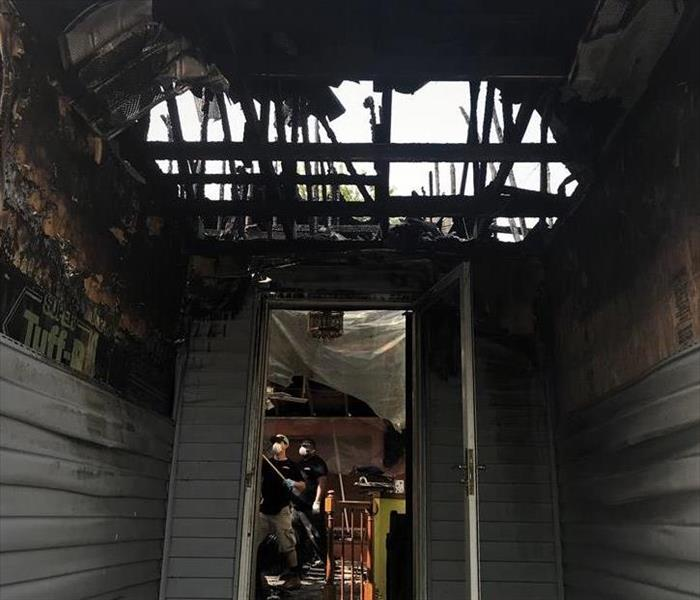 the entrance of a home that suffered extreme fire damage with the roof burnt off and two servpro technicians cleaning inside