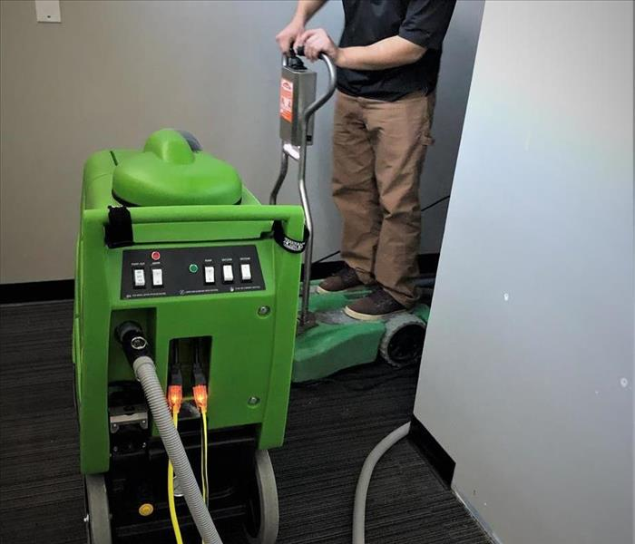 a man in a black polo and khaki pants driving a portable green water extractor hooked up to another larger water extractor