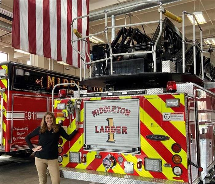 a woman in black SERVPRO shirt and khaki pants standing in front of fire trucks with American flag in background