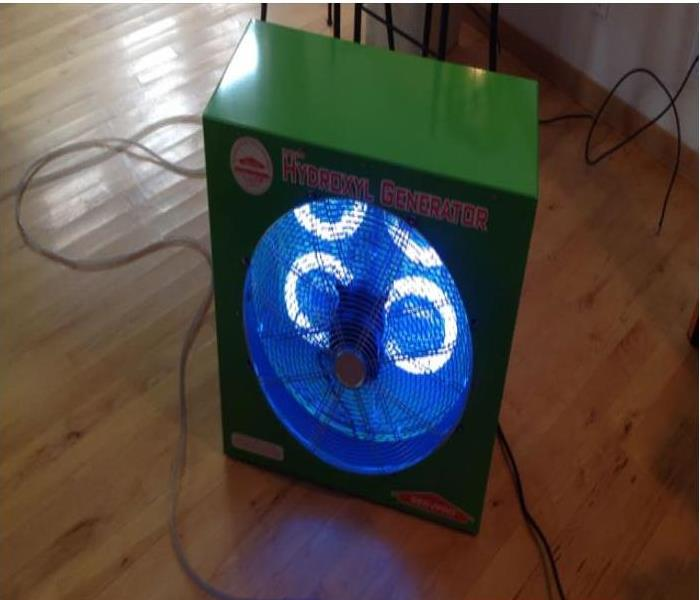 a large green ozone machine with fans it has a blue led light indicating it is working