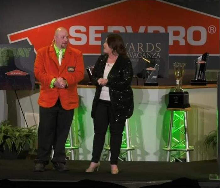 a man and a woman announcing SERVPRO Convention winners of accomplishment he is dressed in an orange sport coat