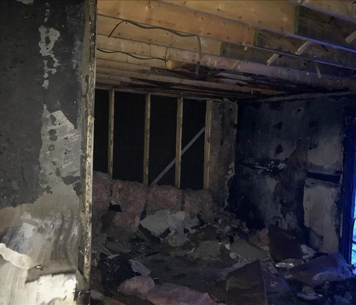 a fire damaged room with burnt and soot covered walls with charred exposed frame