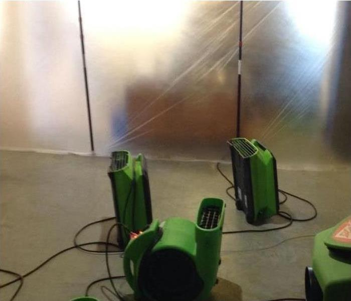 a concrete floor with three green air movers and a green dehumidifier contained within a plastic wall for containment