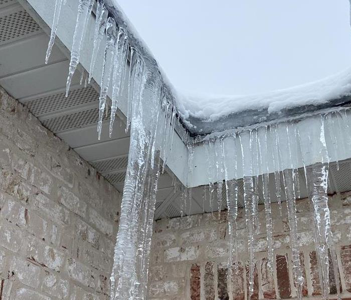 icicles dripping down a white brick house