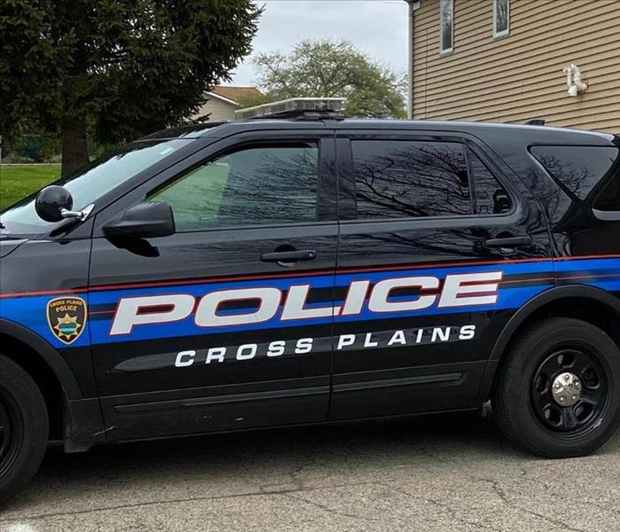 a blue cross plains squad car in front of a tan building