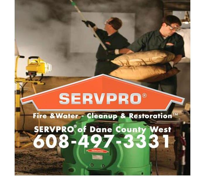 restoration technicians working on a fire damaged property with the servpro of dane county logo and phone number in front