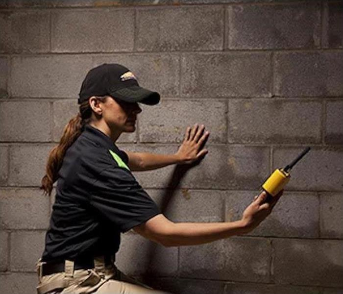 a woman in khaki pants and black servpro shirt standing using a water scoping device to detect moisture in basement