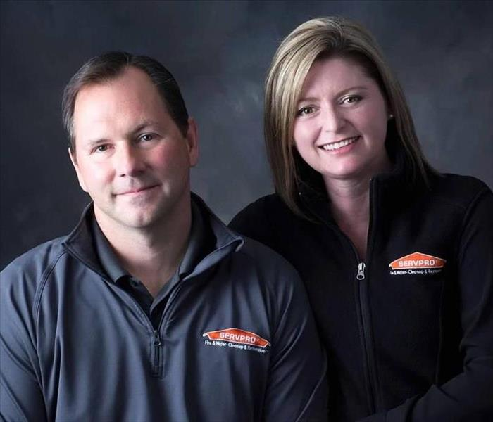 headshots of two people, a dark-haired middle aged man wearing a grey servpro zip down and his partner, a middle aged woman