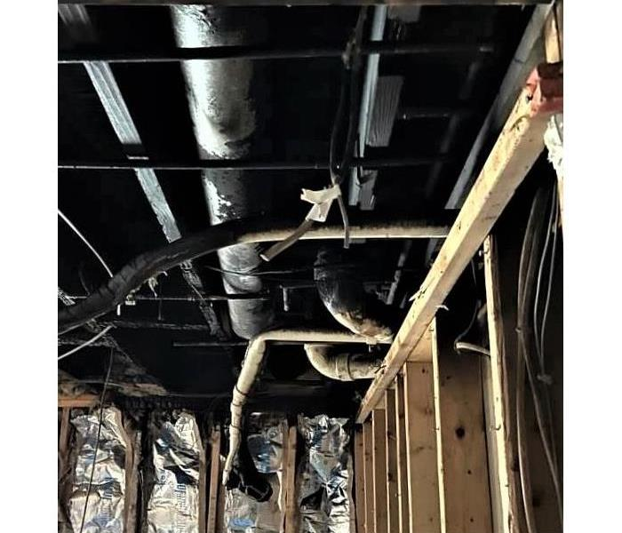 charred and burnt exposed ceiling from an electrical fire