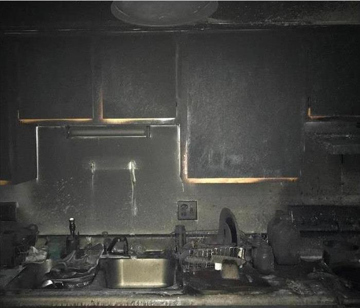 a completely burnt kitchen covered in black soot and ash