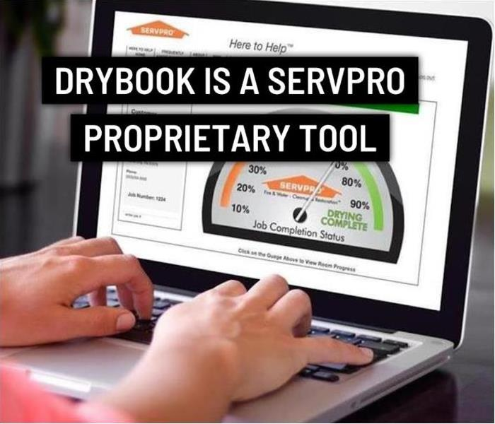 a person typing on a laptop with SERVPRO Dry Book in view